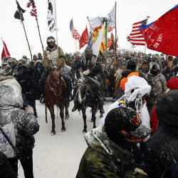"Veterans march with activists near Backwater Bridge just outside the Oceti Sakowin camp during a snow fall as ""water protectors"" continue to demonstrate against plans to pass the Dakota Access pipeline adjacent to the Standing Rock Indian Reservation, near Cannon Ball, North Dakota, U.S., December 5, 2016."