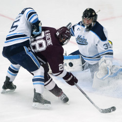 Colgate University's Hunter Racine (center) tries to get a shot past the University of Maine's Rob McGovern (right) while Eric Schurhamer puts high pressure on during their hockey match at Alfond Arena in Orono in January 2016.