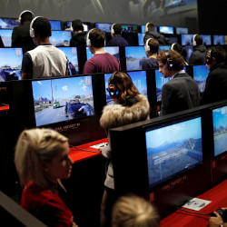 Visitors play the video game Final Fantasy XV at the Paris Games Week, a trade fair for video games in Paris, France, October 26, 2016.
