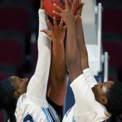 The University of Maine's Tanesha Sutton (left) and Sheraton Jones battle for a rebound with Northeastern during their basketball game at the Cross Insurance Center in Bangor on Wednesday.