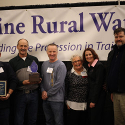 Hugh Kirkpatrick (right), Fred Page III (from left), Russell Plourde, Tim Ouellette and Sue Sands, employees of the Caribou Utilities District, celebrate with Kirsten Hebert (second from right), Maine Rural Water Association director, after winning the association's Best Tasting Water Contest on Thursday at the Cross Insurance Center in Bangor.