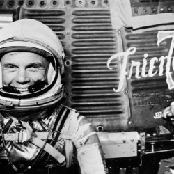 "Astronaut John H. Glenn Jr., pilot of the Mercury Atlas 6 (MA-6) spaceflight, poses for a photo with the Mercury ""Friendship 7"" spacecraft during preflight activities at the Kennedy Space Center in Cape Canaveral, Florida, U.S. before Glenn piloted the Mercury-Atlas 6 ""Friendship 7"" spacecraft on the first manned orbital mission of the United States on Feb. 20, 1962."