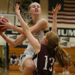 Houlton junior Kolleen Bouchard keeps her eyes on the rim as she slashes to the basket Saturday afternoon in a game against Orono. Bouchard finished with 36 points as Houlton rolled to a 72-50 victory. Defending on the play for Orono is Daphne Murphy.