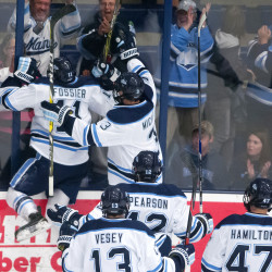 University of Maine's Mitchell Fossier (left) leaps on the board to celebrate scoring his first collegiate goal against Rensselaer Polytechnic Institute during their hockey game on Oct. 7 at Alfond Arena in Orono.