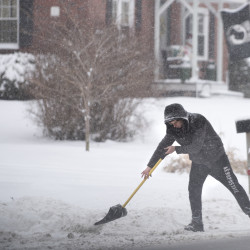 "Travis Anderson shovels snow Monday afternoon in the driveway of his Brewer home. ""I lived here all my life, and I hate this,"" he said about the snow."