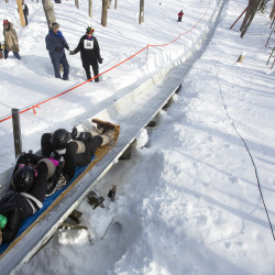 A team zips down the chute during the U.S. National Toboggan Championships at the Snow Bowl in Camden in a 2015 file photo.