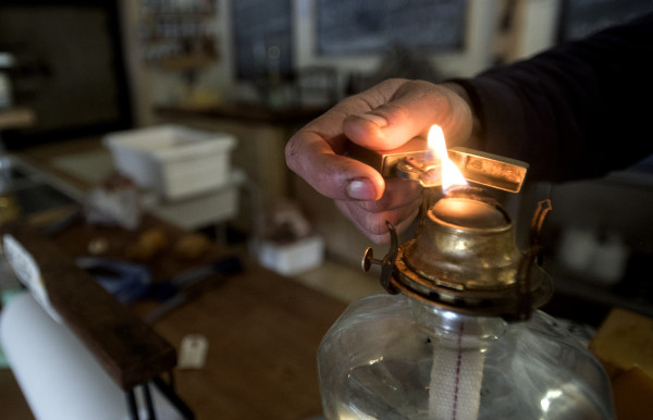 Matthew Secich lights a lantern while waiting on customers at his Charcuterie store in Unity recently.
