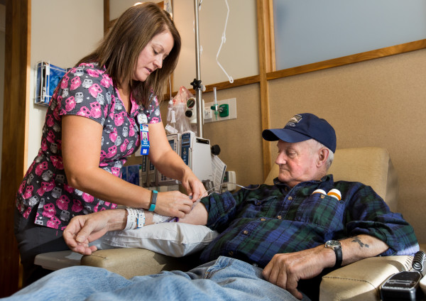 EMMC Cancer Care nurse Tinna Peck adjusts Eugene Dunton, 76, of Burnham during a cancer infusion at the Lafayette Family Cancer Center on Wednesday afternoon following the facility's announcement as the newest member of the Dana-Farber Cancer Care Collaborative that morning. EMMC Cancer Care staff will now have opportunities to consult with medical specialists at the renowned Boston facility, and access to many more of the latest Dana-Farber clinical trials will be available in Maine for patients at EMMC Cancer Care.