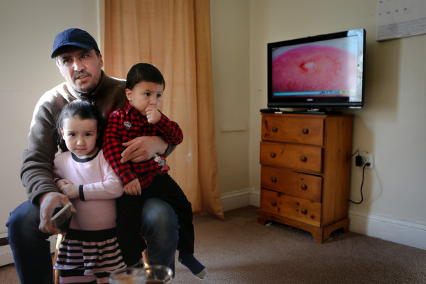 Nadir Alzoubi sits in his Portland living room last month with his son, Omar, 2, and daughter Sundus, 4. Alzoubi and his family were among the first Syrian refugees resettled in Maine since the outbreak of the county's civil war.