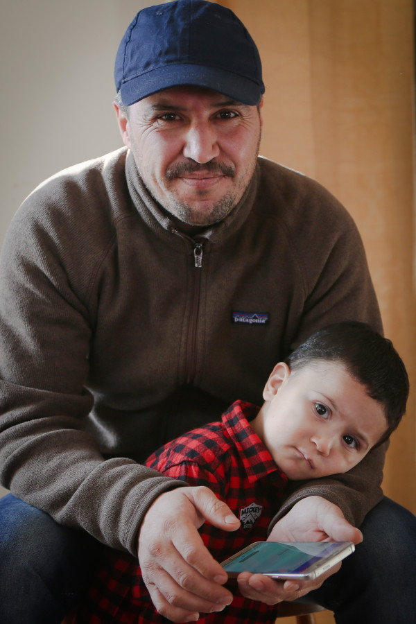 Nadir Alzoubi sits in his Portland living room last month with his son, Omar, 2. Alzoubi and his family were among the first Syrian refugees resettled in Maine since the outbreak of the county's civil war.