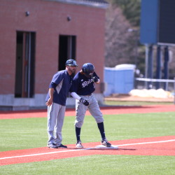 Coach Nick Derba (left) of the University of Maine gives instructions to a baserunner during a 2016 baseball game in Orono. Derba on Saturday was named the Black Bears' interim head coach after Steve Trimper accepted the job at Stetson University in Florida.