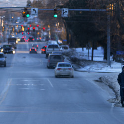 A pedestrian walks along Broadway where there is no sidewalk last week in Bangor.