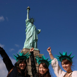 Japanese tourists pose in front of the Statue of Liberty on the 130th anniversary of the dedication in New York Harbor, in New York City, Oct. 28, 2016.