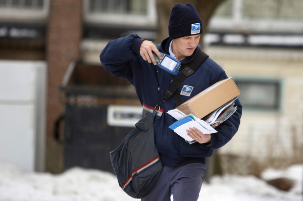 U.S. Postal Service carrier Adam Hall scans a package to deliver along his route Christmas Eve in Brewer.