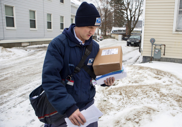 U.S. Postal Service carrier Adam Hall carries a package and mail to deliver along his route Christmas Eve in Brewer.