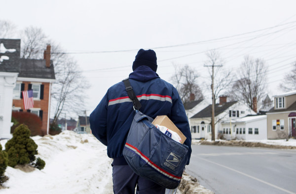 U.S. Postal Service carrier Adam Hall walks to the next house to deliver along his route Christmas Eve in Brewer.