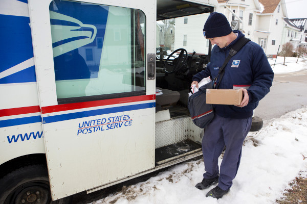 U.S. Postal Service carrier Adam Hall adds a package to his satchel deliver along his route Christmas Eve in Brewer.