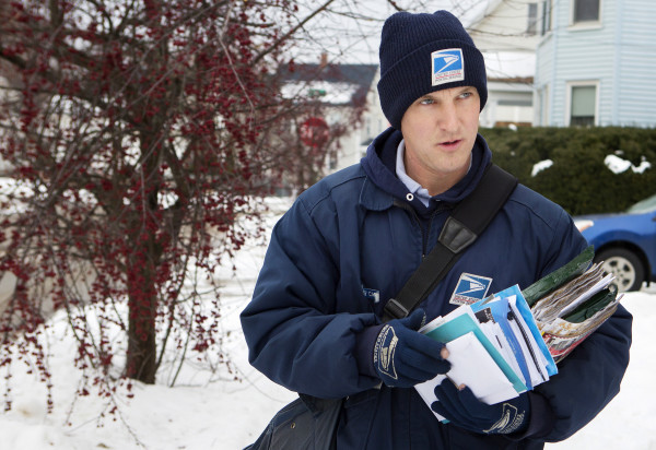 U.S. Postal Service carrier Adam Hall works to deliver along his route Christmas Eve in Brewer.
