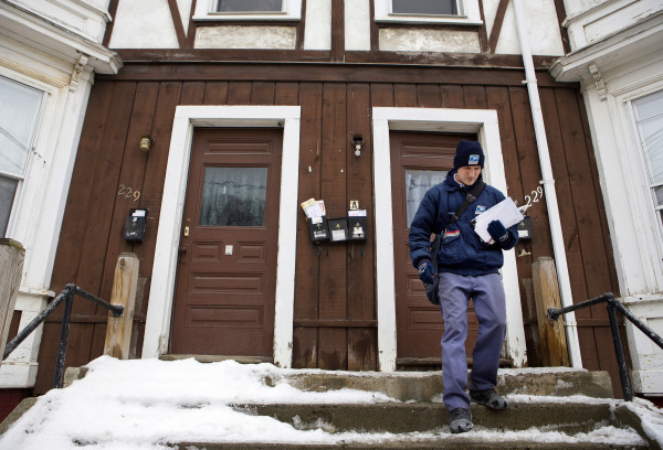 U.S. Postal Service carrier Adam Hall delivers mail along his route Christmas Eve in Brewer.