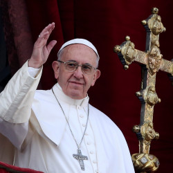 """Pope Francis waves after delivering his """"Urbi et Orbi"""" (to the city and the world) message from the balcony overlooking St. Peter's Square at the Vatican on Dec. 25, 2016."""