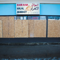 The open sign is lit at Ahram Halal Market on Forest Avenue despite boarded up windows on Tuesday morning in Portland. Police are searching for a man suspected of smashing the windows with a baseball bat on Christmas Eve.