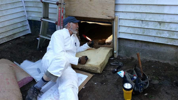 Dave Brown, 75, a volunteer for the Harpswell Aging at Home team, insulates the floor under a house.