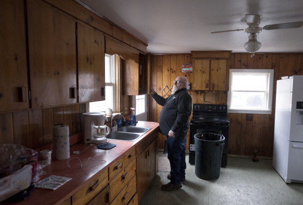 Garry Owen Motorcycle Club President Warren Ard, 59, checks the kitchen cabinets on Wednesday at the Garry Owen House, which offers transitional housing to homeless veterans, in Searsmont.