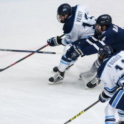 The University of Maine's Nolan Vesey (left) tires to move the puck past New Hampshire's Dylan Maller during their Dec. 3 game at Alfond Arena in Orono Saturday.