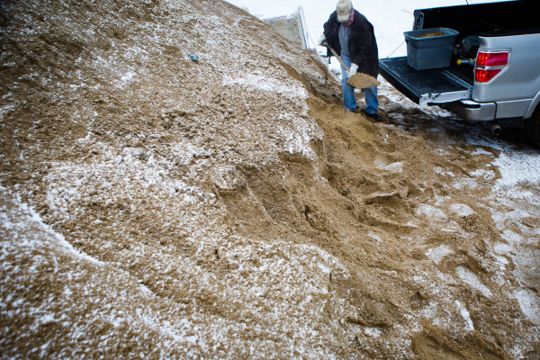 Dick Baker gets his share of salted sand from the public pile in Deering Oaks Park in Portland on Thursday morning as the snow starts to fall.