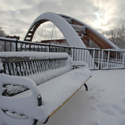 A snow covered bench overlooks the Gateway Crossing Bridge in Riverfront Park in Houlton in this December 2015 file photo. Town Councilors on Tuesday approved an ordinance to prohibit use of tobacco products and smoking in all of the town's parks.