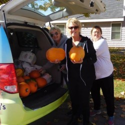 Tammy Goetsch (center), program director for Adopt-a-Block of Aroostook, displays some pumpkins during the Thanksgiving Outreach effort as part of the Adopt-a-Block of Aroostook program.