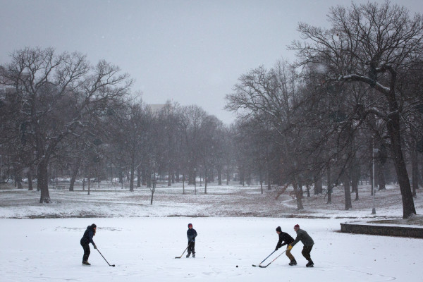 Laura Newman (left) plays hockey with family, Charlie (second from left), 11, Jondall (second from right), 14, and Jeff Norris, on the pond at Deering Oaks Park in Portland on Thursday morning.
