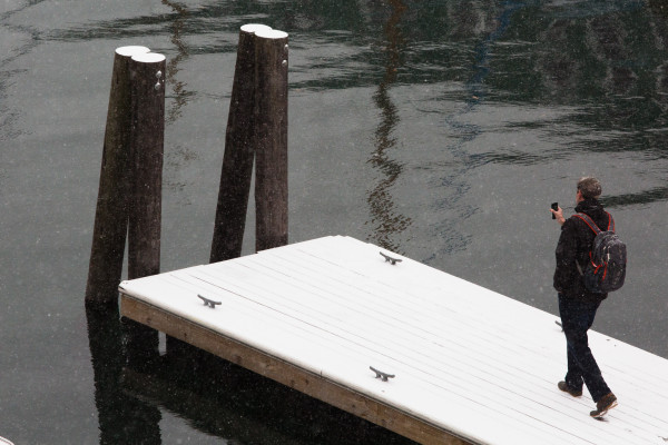 A man takes pictures with his phone on the Portland waterfront on Thursday.