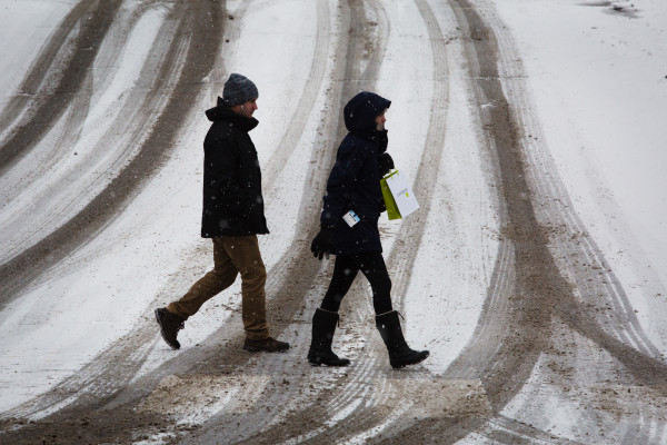 A man and woman cross Pearl Street in Portland on Thursday while a storm starts dumping snow on the city.