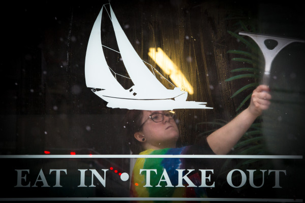 Gemma Dufor squeegees the condensation off the windows at Casco Variety on Commercial Street in Portland on Thursday as the snow falls outside.