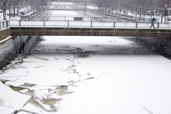 Snow falls as a pedestrian crosses a bridge over the Kenduskeag Stream in downtown Bangor on Thursday.