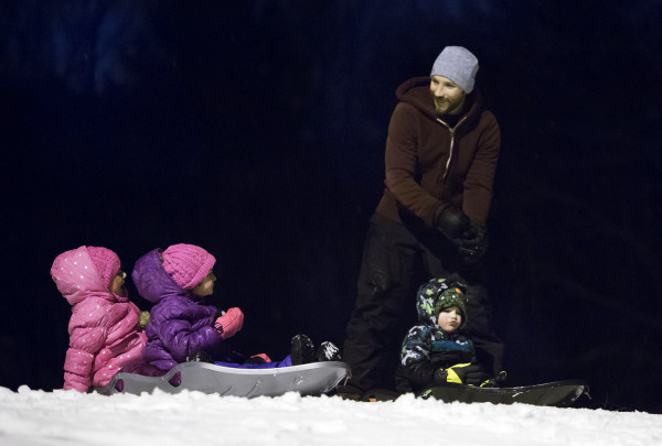 Tim McCann (right) enjoys an evening sledding session with his children Alora (from left), 7, Clare, 4, and Connor, 3, on Thursday at Hayford Park on Union Street in Bangor.
