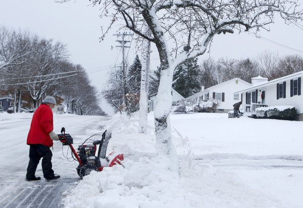 Tom Sargent pushes his snowblower up his driveway in Bangor Friday.