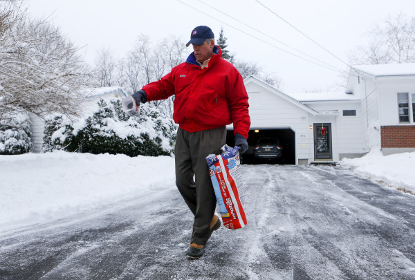 Peter Neal salts his driveway after snowplowing it clear in Bangor Friday.