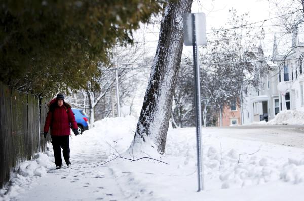 A woman navigates a snowy sidewalk in Bangor Friday morning.