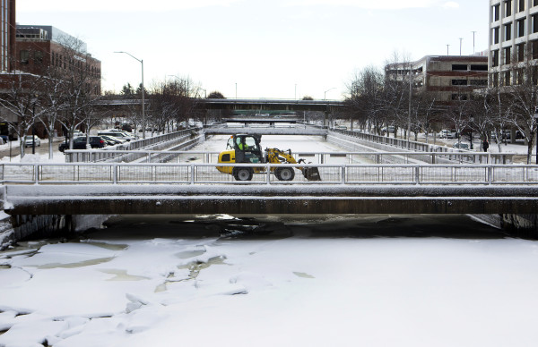 A plow works to remove snow from a bridge in Bangor Friday.