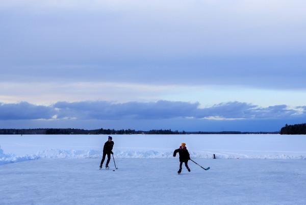 Aiden Rand (left), 13, skates to the puck against his sister Lily Rand, 9, while playing a game of pond hockey on Pushaw Lake in Orono Friday.