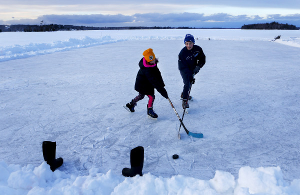 Aiden Rand (right), 13, plays a game of pond hockey with his sister, Lily Rand, 9, on Pushaw Lake in Orono Friday.