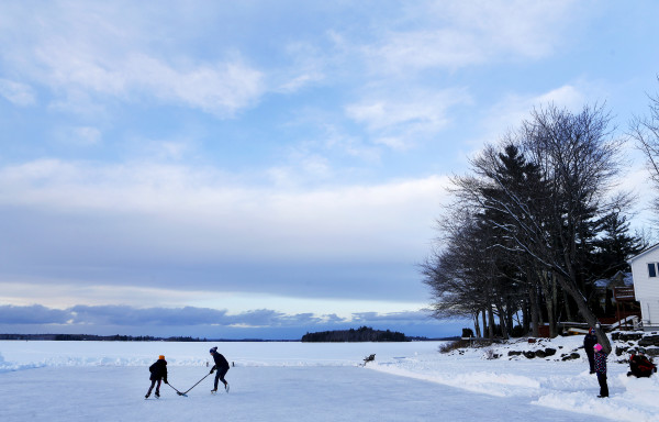 Caleigh Dareies (right), 9, watches as Aiden Rand (center), 13, plays a game of pond hockey with sister, Lily Rand, 9, on Pushaw Lake in Orono Friday.