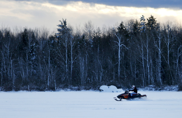 A snowmobiler flies across Pushaw Lake in Orono Friday.