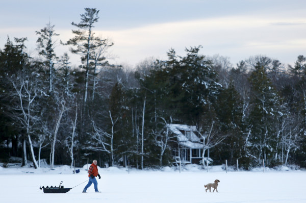 A man and his dog look for places to place ice fishing traps on Pushaw Lake in Orono Friday.