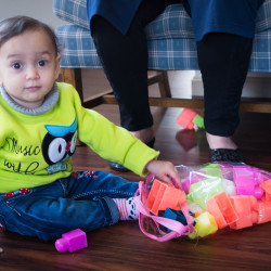 Jena Saker, 1, plays on the floor in her family's Westbrook apartment on Friday. She arrived in the United States with her mother and siblings from Syria, joining her father, on Nov. 1, which was her birthday.
