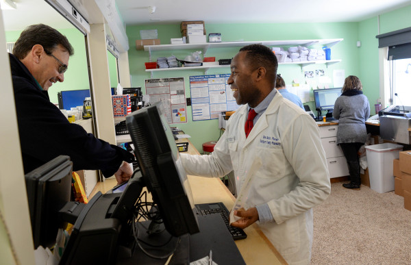 Pharmacist Ben Okafor (right), who was born and raised in Nigeria before moving to Maine in 2007, helps a customer on Dec. 15 at his pharmacy in Eastport.