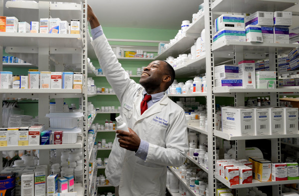 Pharmacist Ben Okafor, who was born and raised in Nigeria before moving to Maine in 2007, reaches for a medication on Dec. 15 at his pharmacy in Eastport.