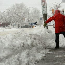 A downtown merchant attempts to keep ahead of Thursday's storm that closed schools and many businesses in Presque Isle and most of Aroostook County.